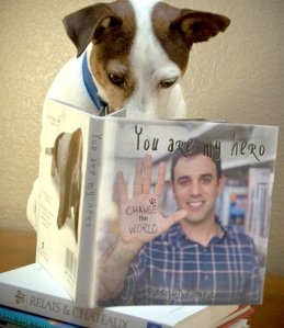 Photograph of a dog reading a book entitled 'You are my hero' with Rodney Habib on the cover